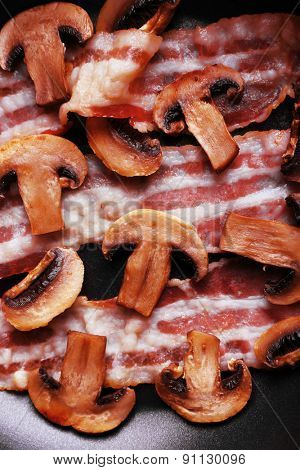 Strips of bacon with mushrooms in pan, macro view