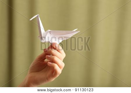 Female hand with paper crane on blurred background