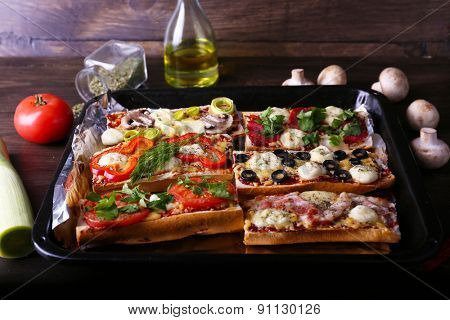 Different sandwiches with vegetables and cheese on pan on table close up