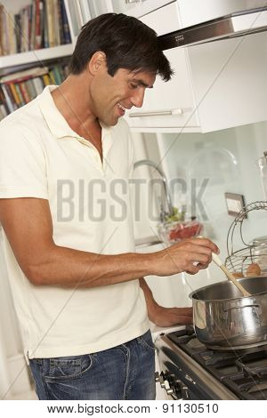 Man Preparing Meal At Cooker