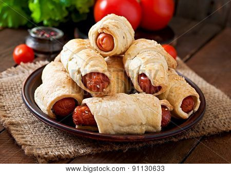 Sausage in the dough sprinkled with sesame seeds on a wooden background in rustic style