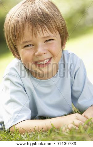 Portrait Of Young Boy Relaxing In Countryside