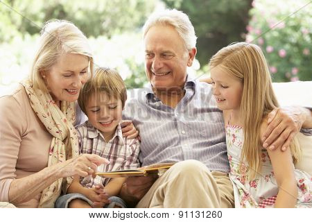 Portrait Of Grandparents Reading To Grandchildren On Sofa