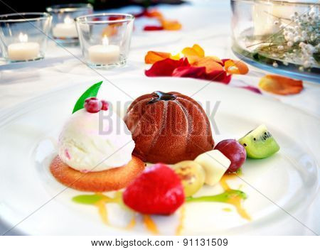 Dessert plate on restaurant table ready. Chocolate ice cream, fruit and biscuits. romantic restauran