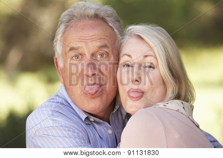 Portrait Of Senior Couple Pulling Faces Outside