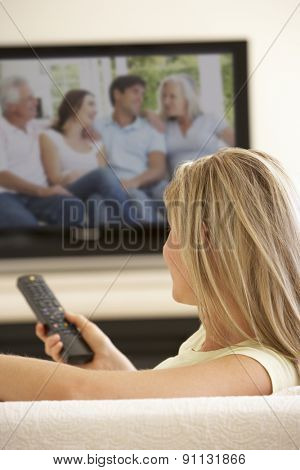 Woman Watching Widescreen TV At Home