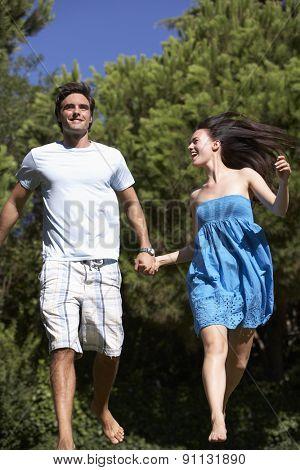 Young Couple Running Through Summer Field