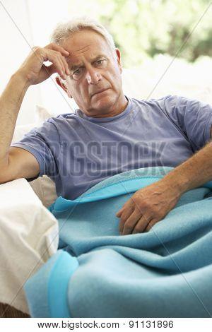 Senior Man Feeling Unwell Resting Under Blanket