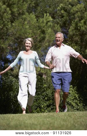 Senior Couple Running Through Summer Field