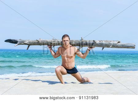 Sporty, healthy and muscled man training on a summer beach