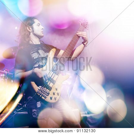 Man playing bass guitar in live concert. Live music background