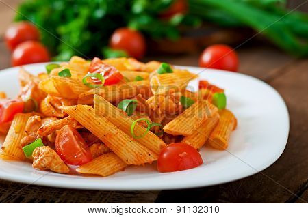 Penne pasta in tomato sauce with chicken and tomatoes on a wooden table