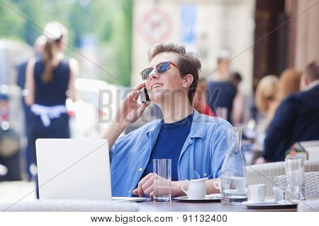 Young Man Sitting In Outside Coffeehouse Talking On Phone