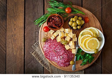 Antipasto catering platter with salami and cheese on a wooden background