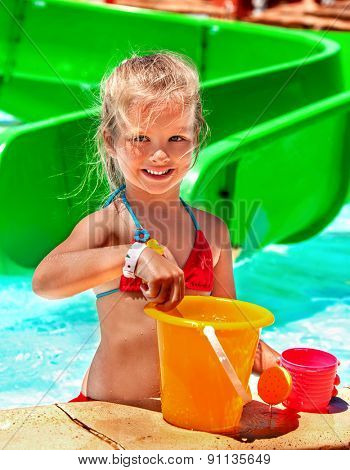 Child playing with bucket in swimming pool.  Summer outdoor.
