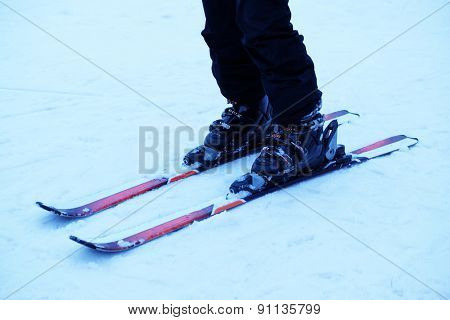 Human legs with skis over white snow background