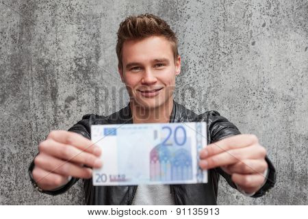 Casual young guy holding 20 euro note