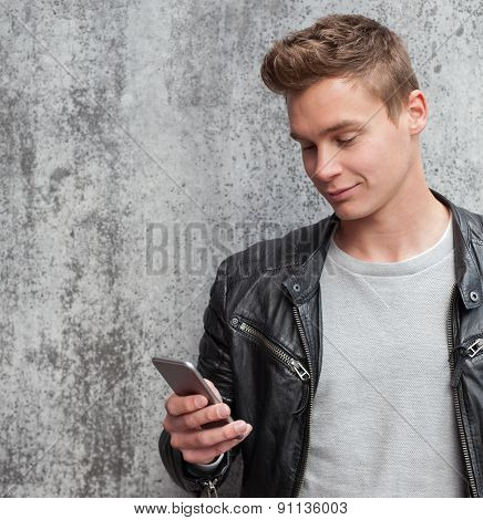 Casual young guy using smart phone