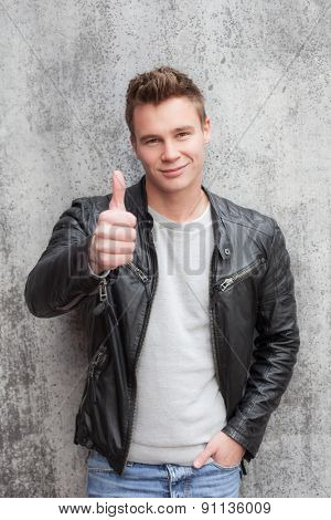 Casual young guy showing thumbs up