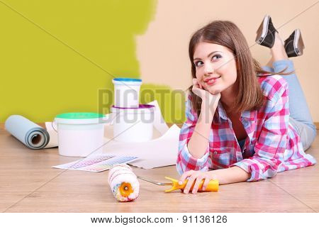 Beautiful girl lying on floor with equipment for painting wall