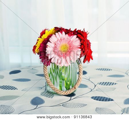 Glass vase of colorful gerbera flowers on table on curtains background