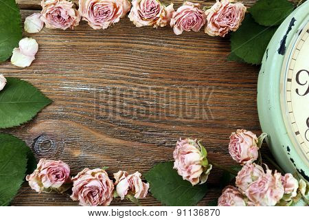Dried roses with green leaves on wooden background