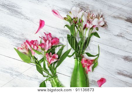 Beautiful alstroemeria in vases on wooden background