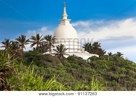Beautiful white temple above green trees, Sri Lanka.