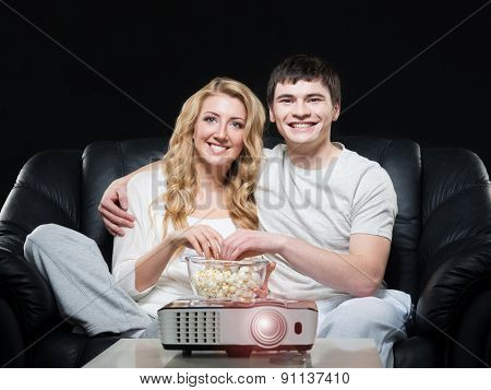 Young family watching a movie or a sport broadcast on a laser projector sitting on a sofa