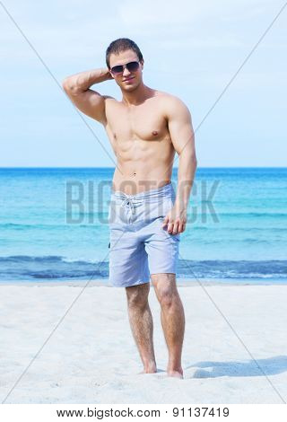 Young, fit, muscled and handsome man on a summer beach