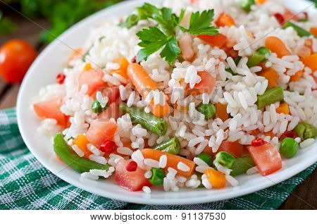 Appetizing healthy rice with vegetables in white plate on a wooden background. Selective focus.