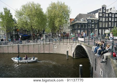 Young People Sit On Bridge Over Amsterdam Canal While Small Boat Passes By