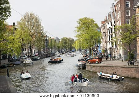 Amsterdam Canal Full With Boats On A Sunny Day In Spring