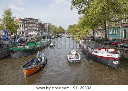 Many Boats Ride On Canal In Amsterdam On A Sunny Day In Spring