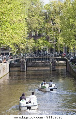 Tourists Paddle In Water Bikes In Amsterdam Canal In Spring