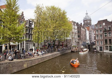 People In Amsterdam Red Light District Sit On Terrace And In Boats