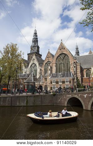 Boat In Canal Near Old Church In Amsterdam Red Light District