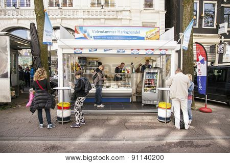 People Enjoy Fresh Herring At Stall In Centre Of Amsterdam