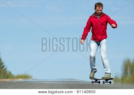Young man riding the skateboard at sunny day