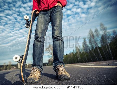 Rider standing on the asphalt road and holding skate board over the blue sky background
