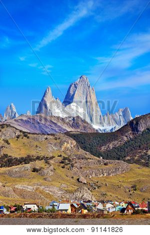 Famous rock Fitz Roy peaks in the Andes. Magnificent panorama of snow-capped mountains in Patagonia. At the foot of the mountains is a small tourist village of El Chalten