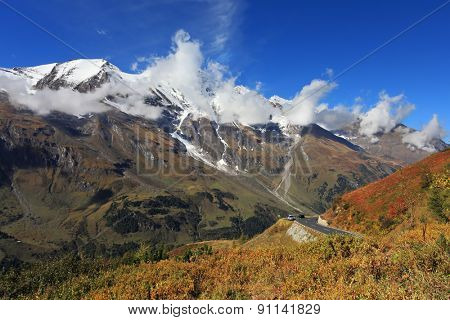 Austrian Alps. Excursion to the picturesque panoramic way Grossglocknershtrasse. Sunny day in early autumn. The mountain slopes are overgrown with grass yellowed
