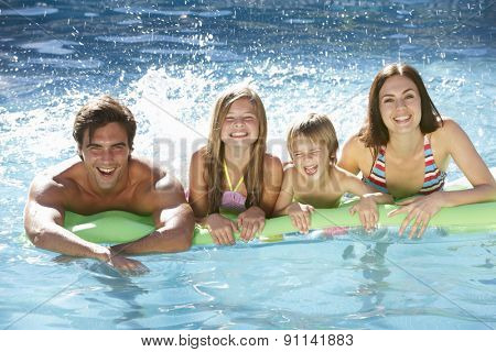 Family Relaxing In Swimming Pool Together