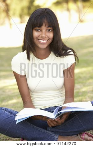 Female College Student Sitting In Park Reading Textbook