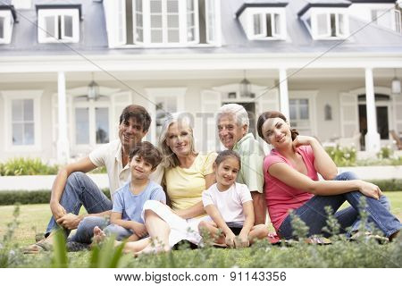 Couple Sitting Outside House On Lawn