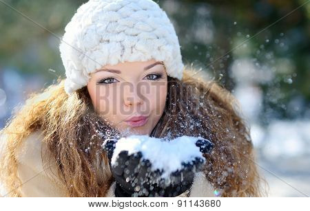 Girl Wearing Warm Winter Clothes And Hat Blowing Snow In Winter Forest