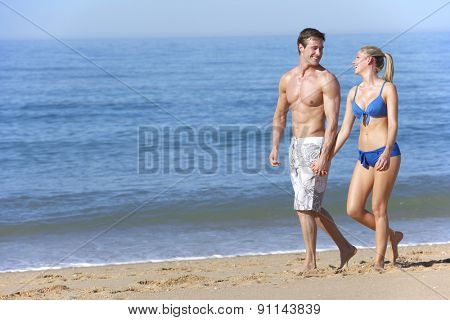 Young Couple Walking Along Summer Beach