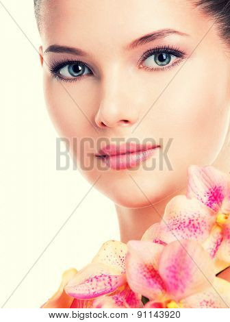 Closeup portrait of beautiful young woman with healthy skin and pink flowers on body - isolated on white.