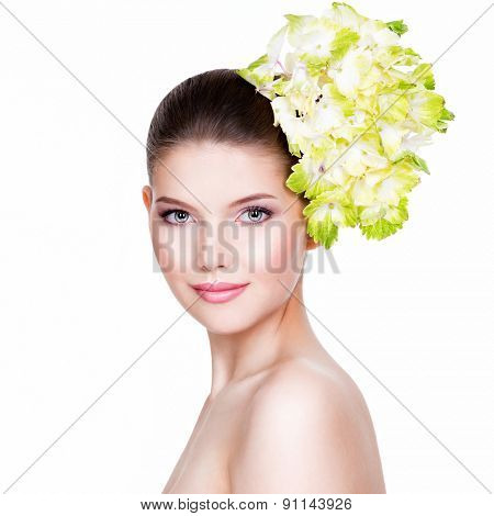 Portrait of young beautiful woman with a healthy clean skin. Pretty woman with flower near the face - isolated on white background.