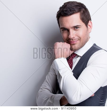 Portrait of young businessman in gray suit with hand near face poses over wall.